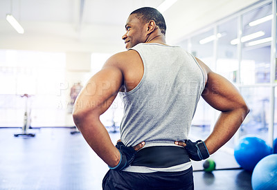 Buy stock photo Rearview shot of a handsome young athletic man standing with his hands on his hips in the gym