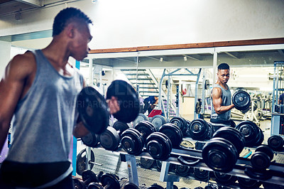 Buy stock photo Cropped shot of a handsome young athletic man watching himself in the mirror while working out with dumbbells in the gym
