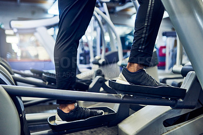 Buy stock photo Cropped shot of an unrecognizable athletic man working out on an elliptical machine in the gym