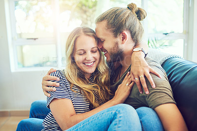 Buy stock photo Shot of a happy and affectionate young couple relaxing together on the sofa at home