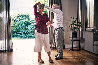 Buy stock photo Full length shot of an affectionate senior couple dancing in their retirement home
