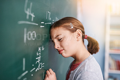 Buy stock photo Cropped shot of a stressed young elementary school kid writing answers to math questions on a green chalkboard in the classroom