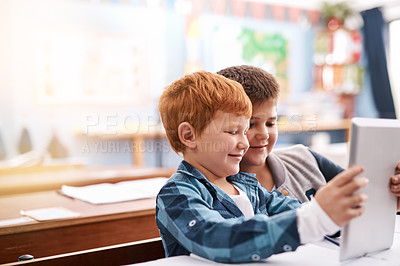 Buy stock photo Cropped shot of two elementary school children browsing on a digital tablet inside of the class during the day