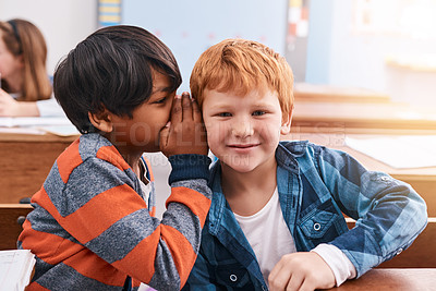 Buy stock photo Cropped shot of elementary school kid whispering into another student's ear inside of the classroom