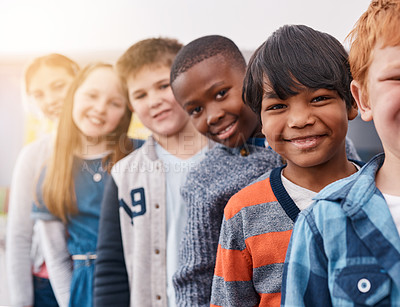 Buy stock photo Portrait of a group of cheerful elementary school kids standing behind each other while looking at the camera