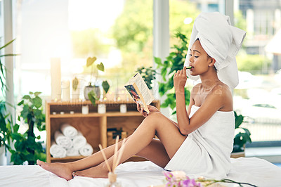 Buy stock photo Shot of an attractive young woman reading a book and eating a slice of cucumber at a spa