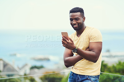 Buy stock photo Shot of a handsome young man using his cellphone while  relaxing outdoors on holiday