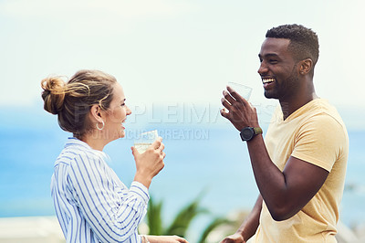 Buy stock photo Shot of a young couple enjoying drinks together while relaxing outdoors on holiday