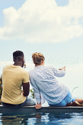 Buy stock photo Rearview shot of a young couple enjoying drinks together while relaxing outdoors on holiday