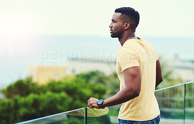 Buy stock photo Shot of a handsome young man looking at the scenery while relaxing outdoors on holiday