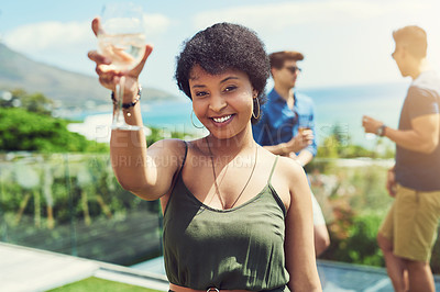 Buy stock photo Portrait of an attractive young woman raising up her glass for a toast while relaxing outdoors with her friends