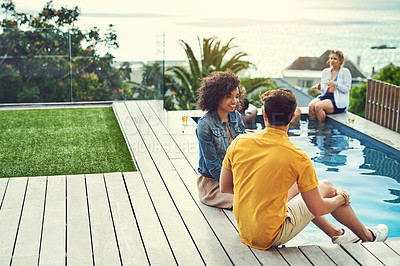 Buy stock photo Shot of a group of friends having drinks and enjoying themselves poolside on holiday