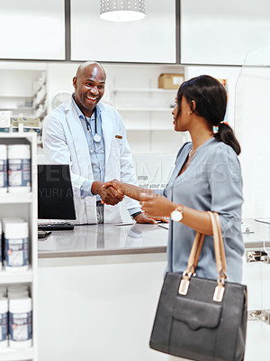 Buy stock photo Shot of a pharmacist and a customer shaking hands in a chemist