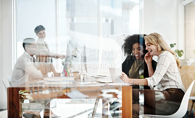 Buy stock photo Shot of two businesswomen working on a digital tablet with their colleagues in the background in an office