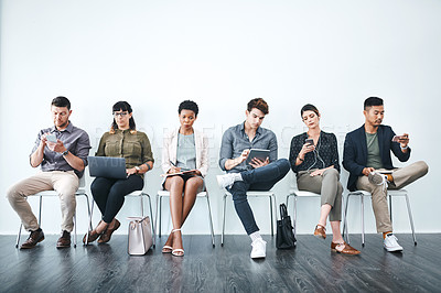 Buy stock photo Studio shot of a group of businesspeople using wireless technology in a waiting room