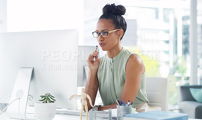 Buy stock photo Shot of an attractive young businesswoman looking thoughtful working at her desk in a modern office