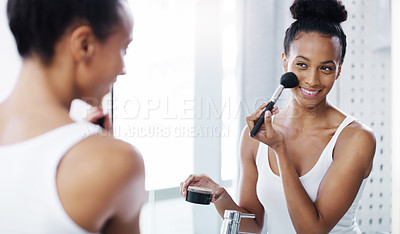 Buy stock photo Shot of an attractive young woman applying make up to her face in her bathroom at home