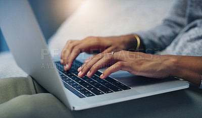 Buy stock photo Shot of an unrecognizable woman using her laptop while relaxing on her bed at night
