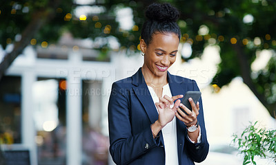 Buy stock photo Shot of an attractive young businesswoman using her cellphone while standing outdoors in the city