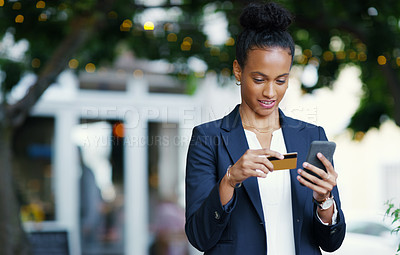 Buy stock photo Shot of an attractive young businesswoman using her cellphone and credit card while standing outdoors in the city