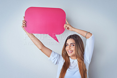 Buy stock photo Portrait of an attractive young woman holding up a speech bubble against a blue background