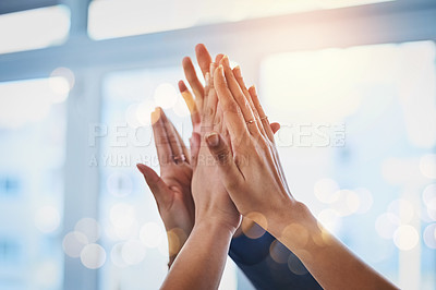 Buy stock photo Shot of a group of unrecognizable businesspeople raising up their arms and joining their hands together in unity at work