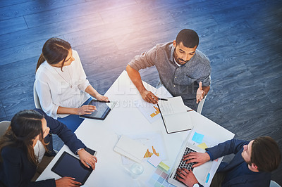 Buy stock photo High angle shot of a group of young businesspeople having a boardroom meeting at work