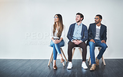 Buy stock photo Full length shot of a group of young businesspeople waiting in line for a job interview