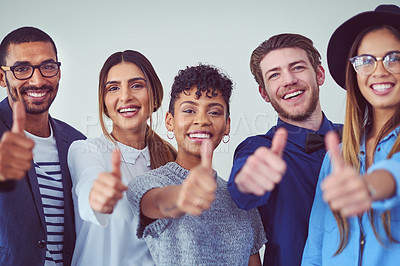 Buy stock photo Closeup portrait of businesspeople showing a thumbs up against a gray background