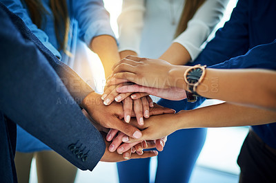 Buy stock photo Cropped shot of a group of colleagues joining heir hands together in unity
