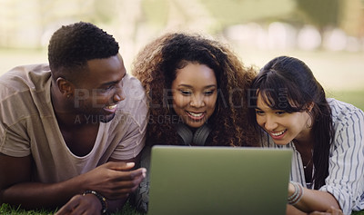 Buy stock photo Shot of a group of friends lying down and using a laptop together while relaxing outdoors