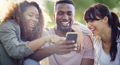 Buy stock photo Shot of a cheerful group of friends using a cellphone together while relaxing outdoors