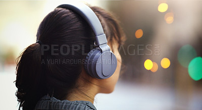 Buy stock photo Closeup shot of an unrecognizable woman listening to music on her headphones while walking through the city