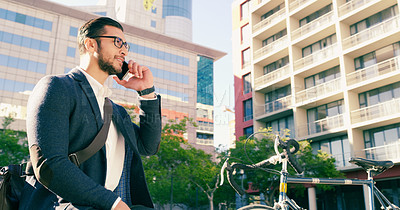 Buy stock photo Shot of a handsome young businessman taking a phone call while walking through the city