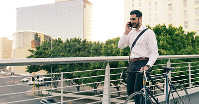 Buy stock photo Shot of a handsome young businessman taking a phone call while commuting to work with his bicycle
