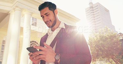 Buy stock photo Shot of a handsome young businessman using his cellphone while walking through the city