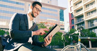 Buy stock photo Shot of a handsome young businessman using his digital tablet while sitting down next to his bicycle in the city