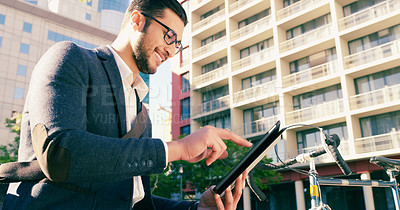 Buy stock photo Shot of a handsome young businessman using his digital tablet while commuting to work on his bicycle