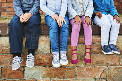 Buy stock photo Shot of a group of unrecognizable elementary school kids sitting on a brick wall outside