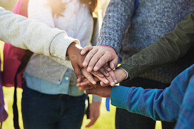 Buy stock photo Shot of a group of unrecognizable elementary school kids joining their hands together in a huddle outside