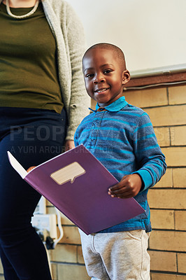 Buy stock photo Shot of an elementary school boy standing alongside her teacher and reading in front of her class