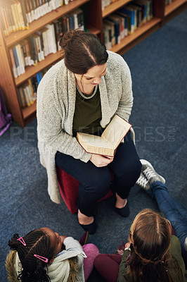 Buy stock photo High angle shot of a teacher reading to a group of elementary school kids in the library