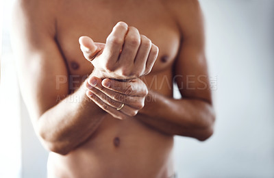 Buy stock photo Shot of a shirtless unrecognizable man holding his wrist in discomfort due to pain inside at home