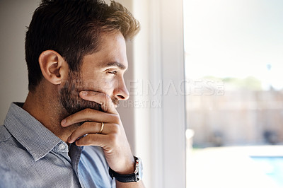 Buy stock photo Shot of a focused young man looking through a window while contemplating inside at home during the day