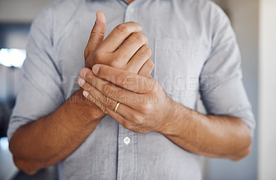 Buy stock photo Shot of an unrecognizable man holding his wrist in pain while relaxing at home
