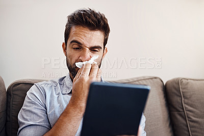 Buy stock photo Shot of a sickly young man blowing his nose with a tissue while browsing through his digital tablet at home