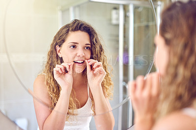Buy stock photo Shot of a young woman flossing her teeth in the bathroom at home