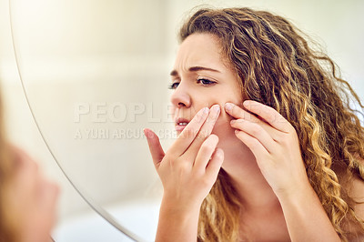 Buy stock photo Shot of a young woman squeezing a pimple on her face in the bathroom at home