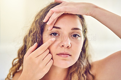 Buy stock photo Portrait of an attractive young woman putting in her contact lenses at home