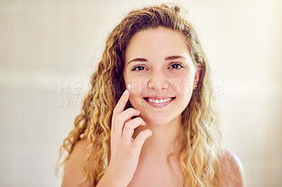 Buy stock photo Portrait of an attractive young woman applying moisturizer to her face in the bathroom at home